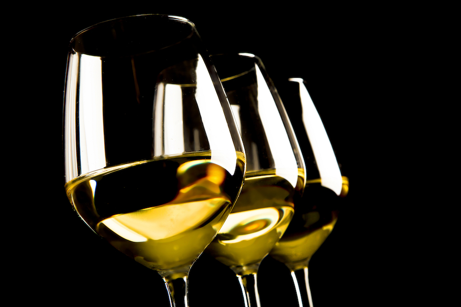three glasses of white wine on black background
